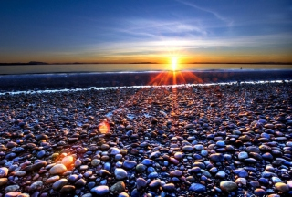 Beach Pebbles In Sun Lights At Sunrise Picture for Android, iPhone and iPad