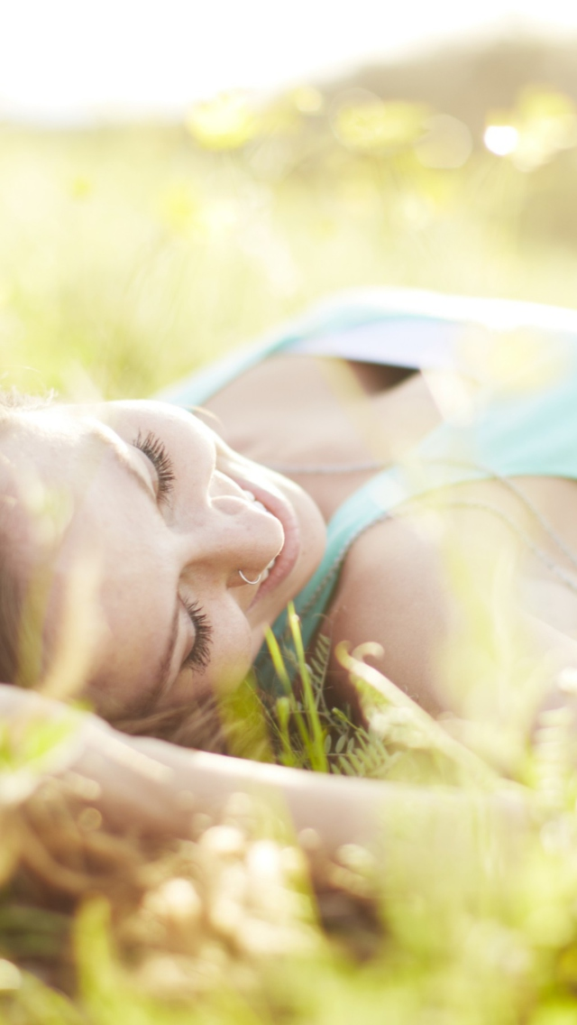 Happy Girl Lying In Grass In Sunlight wallpaper 640x1136