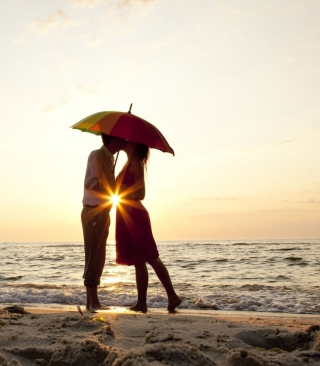 Couple Kissing Under Umbrella At Sunset On Beach - Obrázkek zdarma pro 320x480