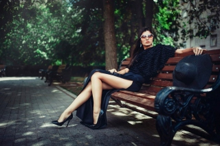 Brunette model posing on bench sfondi gratuiti per 1366x768