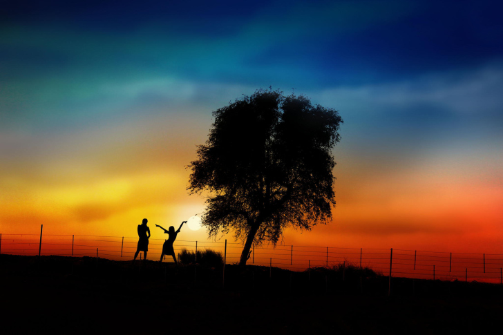 Das Couple Silhouettes Under Tree At Sunset Wallpaper