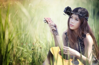 Kostenloses Pretty Girl In Grass Playing Guitar Wallpaper für Android, iPhone und iPad