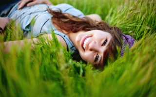 Free Smiling Girl Lying In Green Grass Picture for Android, iPhone and iPad