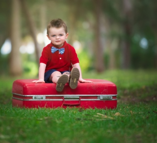 Cute Boy Sitting On Red Luggage - Obrázkek zdarma pro iPad