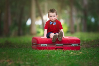 Cute Boy Sitting On Red Luggage papel de parede para celular