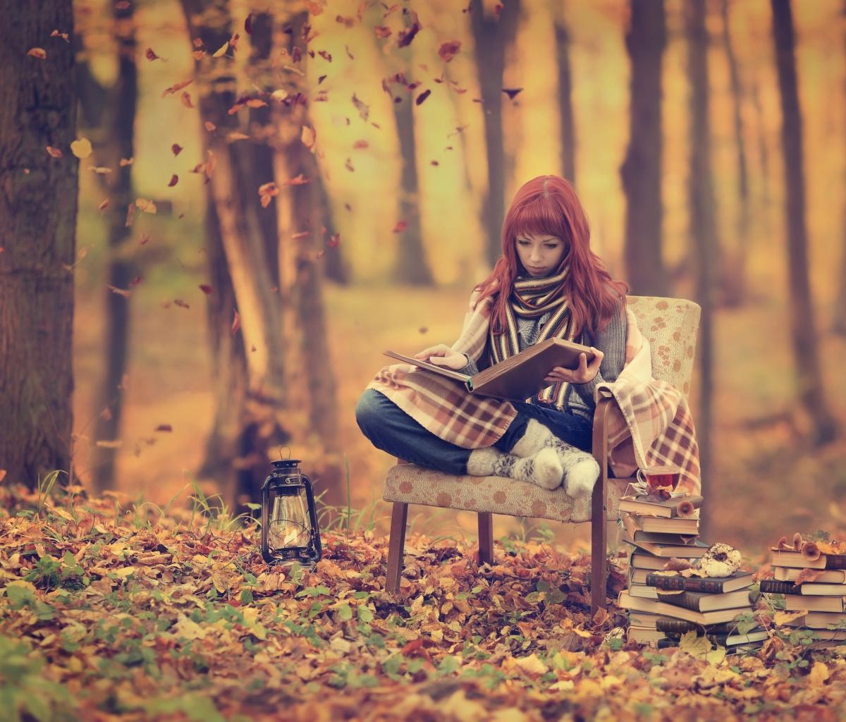 girl reading old books in autumn park