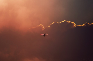 Airplane In Red Sky Above Clouds - Obrázkek zdarma